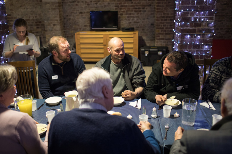 Guests and volunteers chat at a communal table at St Elizabeth of Portugal church, part of the newly opened Glass Door circuit in Richmond.