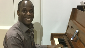 Kwaku plays piano at Rivercourt Methodist Church night shelter